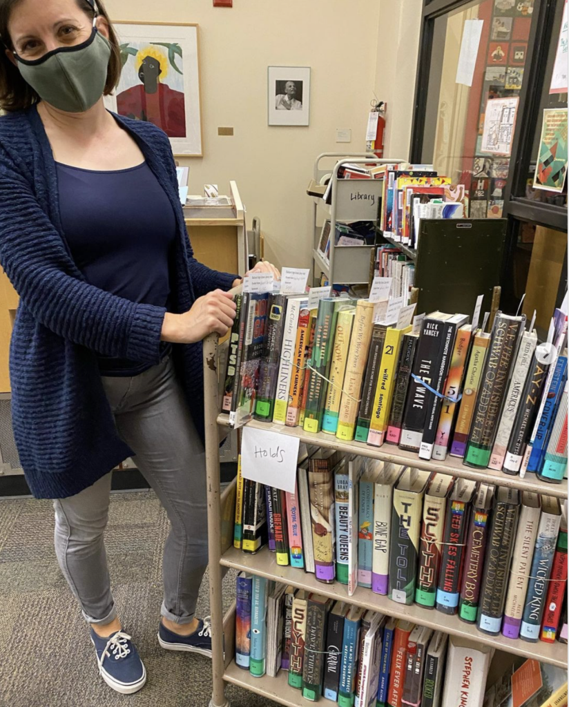 Ms Elam with a cart of books in the library